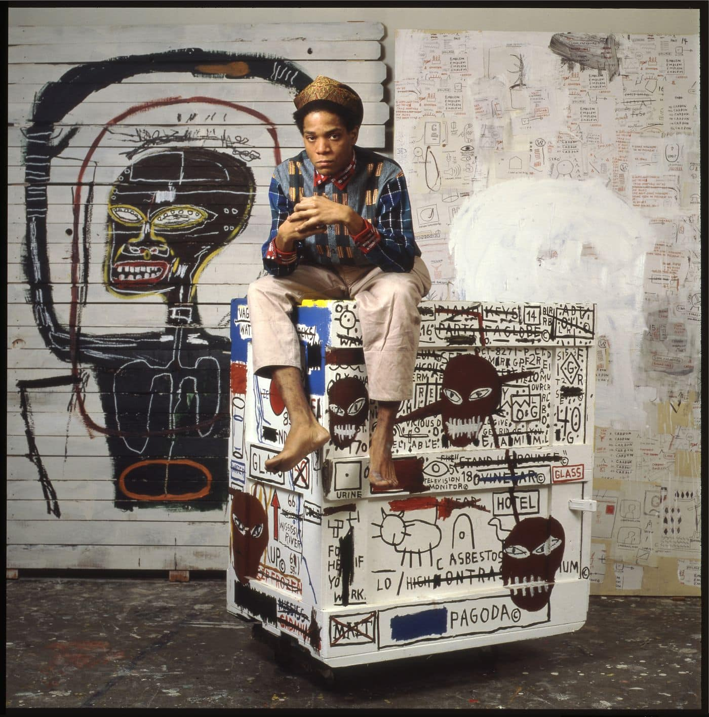 Fotografía de Jean-Michel Basquiat con sus pinturas